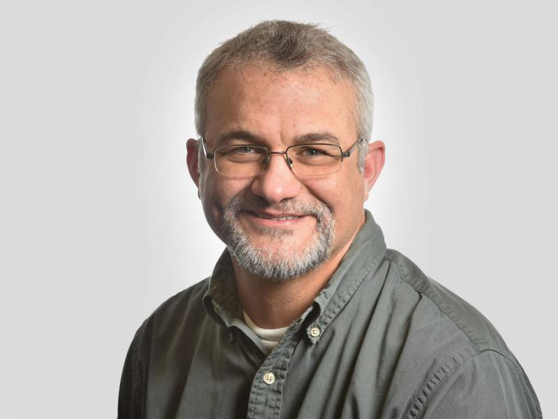 Smiling white man in gray shirt with gray hair/beard and glasses