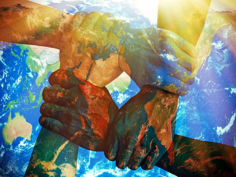 An illustration shows different colored hands united over an image of the earth