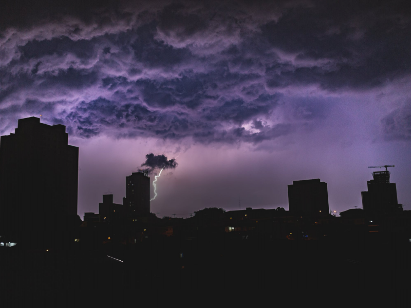 Dark image of a thunderstorm over a cityscape