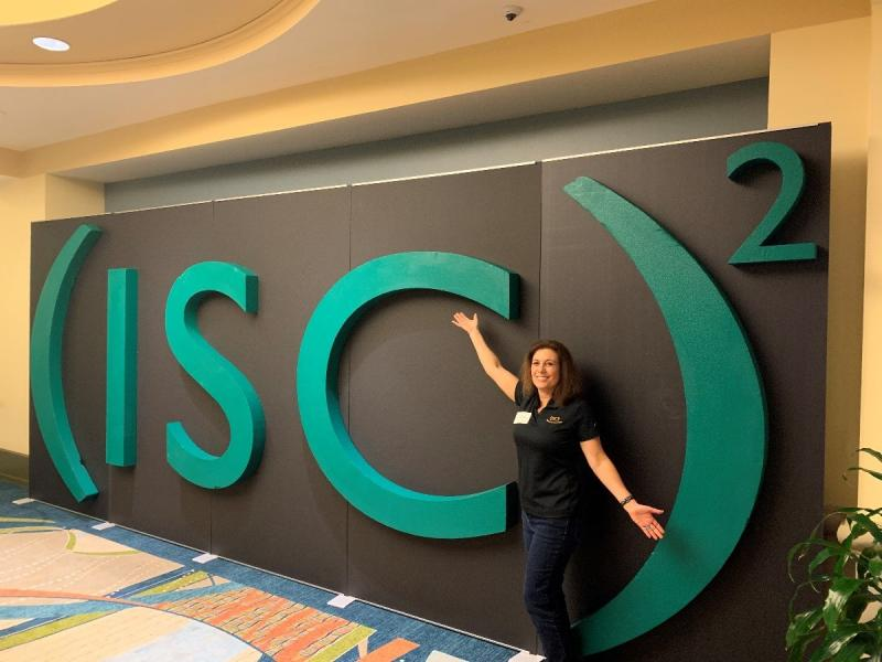 a woman standing in front of a green sign that says ISC2